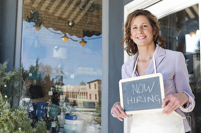 Woman standing outside restaurant with a now hiring sign