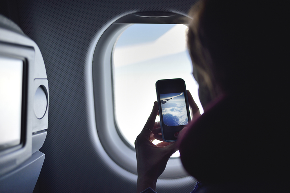 Woman taking photo on plane with iPhone
